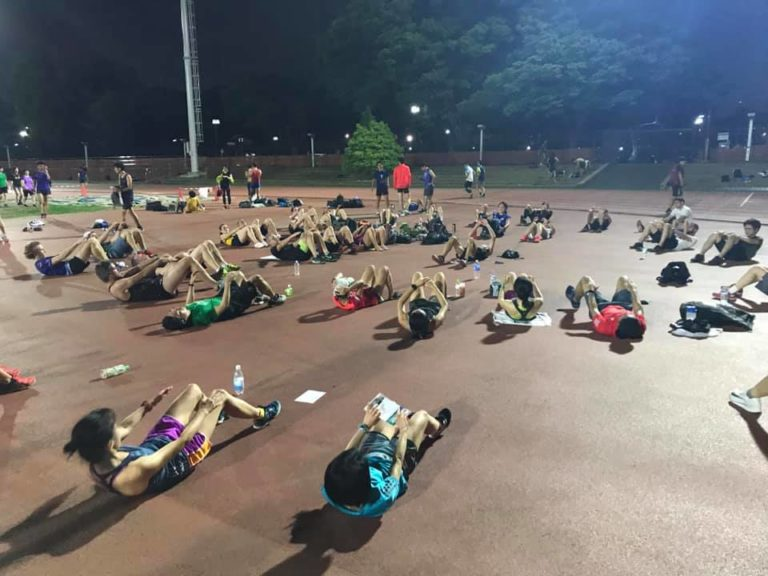 Group of runners stretching on a track