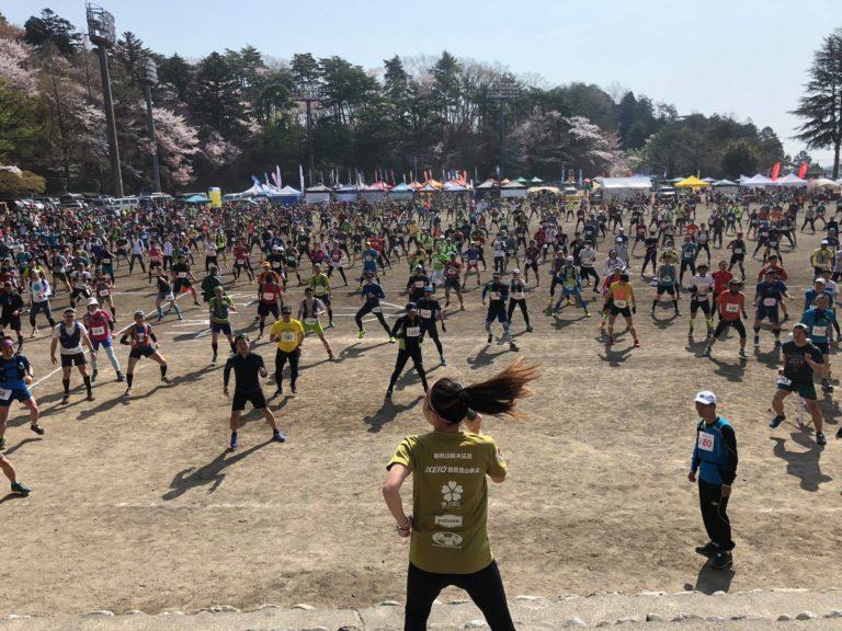 Back shot of group exercises on sandy field