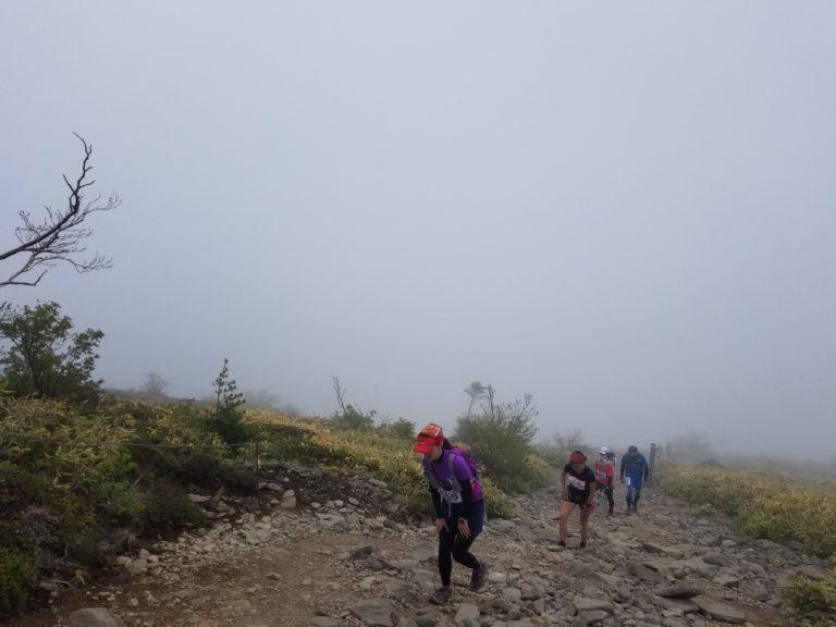 Trail runners climbing foggy mountain