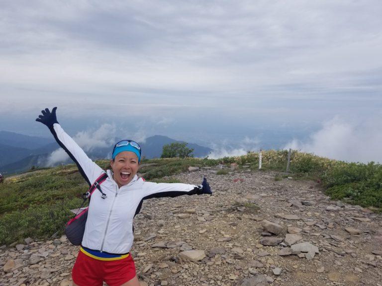 Overjoyed woman at peak of mountain