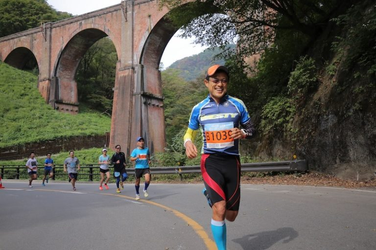 Male runner in Japan with bridge in background