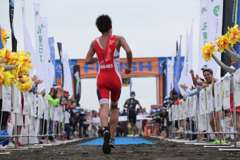Backshot of man running to finish line