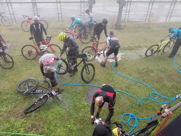Cyclists cleaning bikes with hoses outside