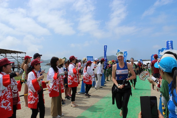 Ise Shima Triathlon participants running past cheering fans