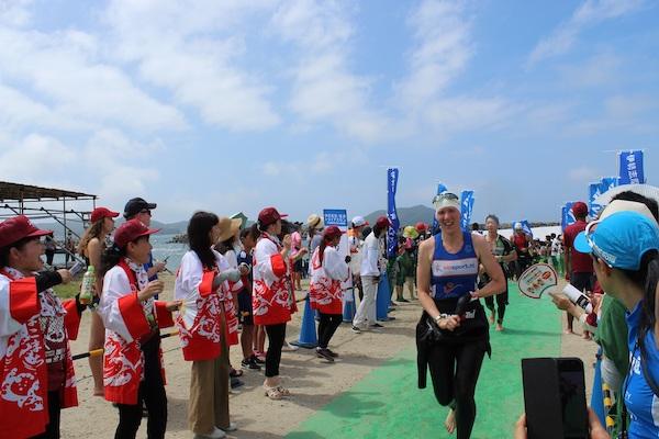 Ise Shima Triathlon participants running past cheering fans