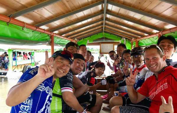 Cyclists on buffalo-drawn cart in Iriomote