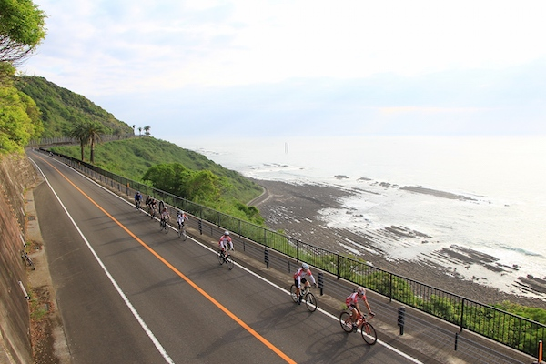 Group of cyclists along coast in Japan