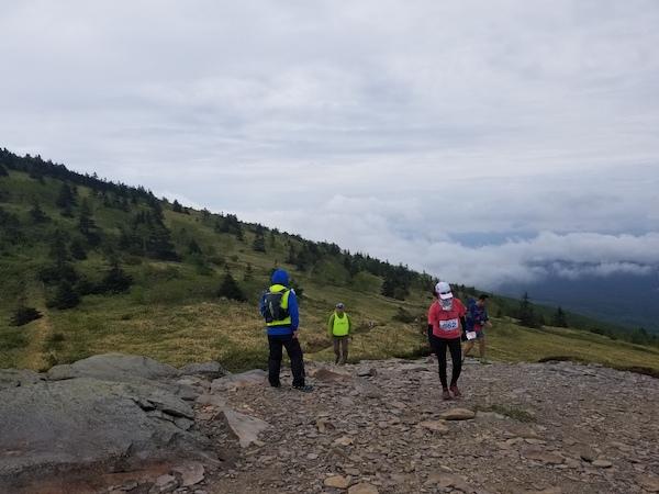 Trail runners climbing mountain gravel