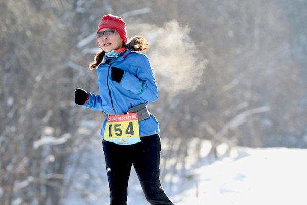 Woman running in snow in Hokkaido
