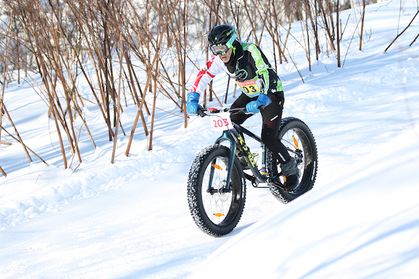 Cycling downhill on mountain bike in snow
