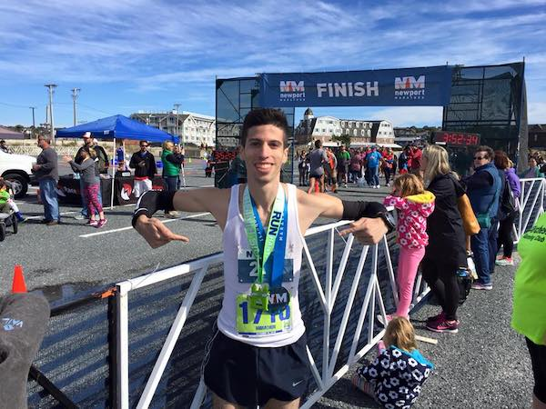 Man at finish line of marathon with finisher medal
