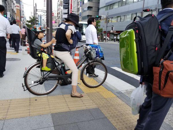 pedestrian riding bike with her child