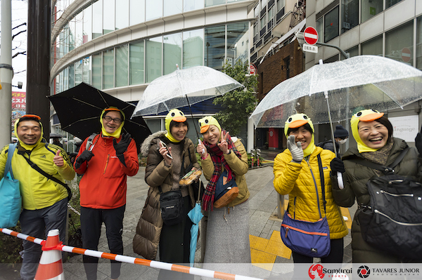 spectators in rain at Tokyo marathon