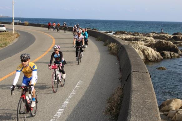 cyclist riding next to coast